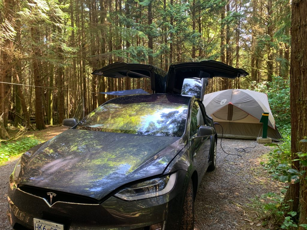 Electric car plugged in beside tent