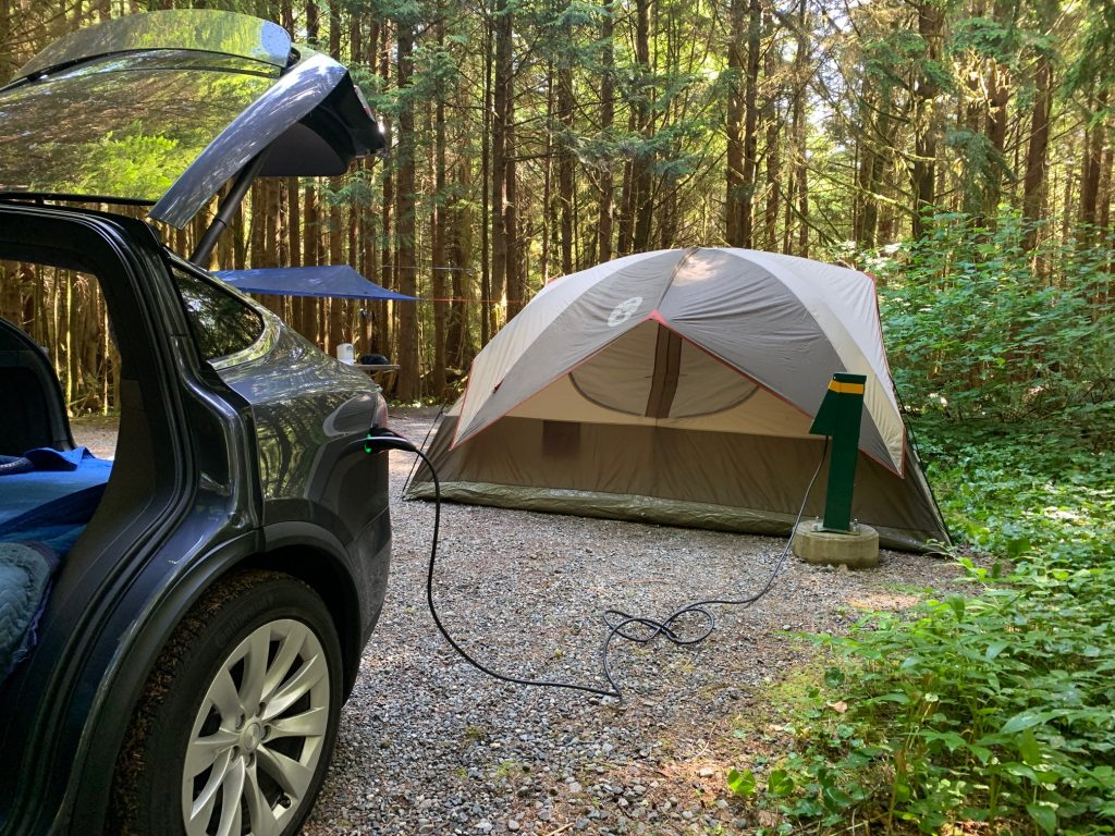 Car plugged in beside tent